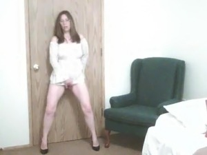 Mature rubs her pussy while standing against the door