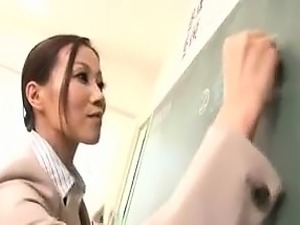 Beautiful Asian teacher writes on the blackboard during a c